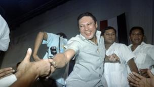 This photo taken on February 12, 1988 in Panama City shows General Manuel Antonio Noriega reaching down to shake hands of followers who attended Noriega's birthday party held by government officials and party workers.
