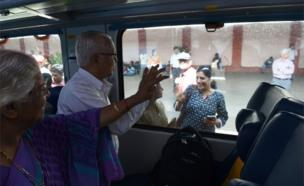 In this photograph taken on May 22, 2017, Indian passengers wave to relatives onboard the Tejas Express luxury train during its first journey between Mumbai and Goa in Mumbai.