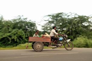 A man on a scooter with his family.