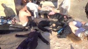A man sits in the middle of bodies with his hands covering his face