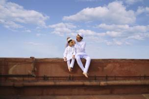 صورة من مسجد في نيودلهي في الهند لأب وابنه يجلسان خارج المسجد في عيد الفطر