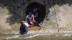 Un manifestante que cruzó el Guaire recibe asistencia al desplomarse frente a un desagüe que da al río.