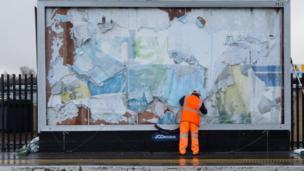 Man removing posters at Lewisham station