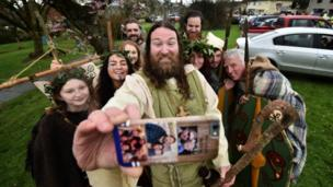 St Patrick, played by actor Marty Burns, took a selfie with members of the Magnus Vikings Association in Downpatrick, Northern Ireland