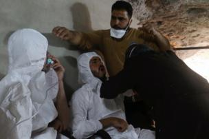 A man breathes through an oxygen mask as another one receives treatment, after what rescue workers described as a suspected gas attack