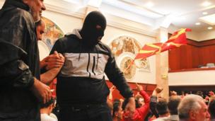Yüzü maskeli bir Makedon protestocu.