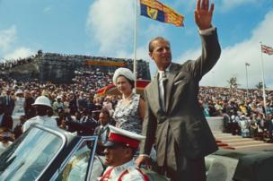During a royal visit, British monarch Queen Elizabeth II and her husband, Prince Philip, Duke of Edinburgh, wave from an open-top convertible to onlookers at Clifford Park, Nassau, Bahamas, 28 February 1966.