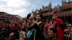 Người xem chụp ảnh xác heo được trang trí và đưa đi diễu hành ở quận Sanxia, ở Tân Đài Bắc, Đài Loan, 0/02/2017.