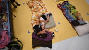 Jennifer Miller and her daughter Jubilee rest laying on the floor of a makeshift shelter at the Timberlin Creek Elementary School in St. Augustine, Florida, on October 6, 2016