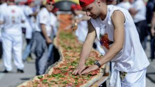 A man adds topping to the giant pizza in Naples.