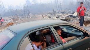 Gente en un coche en Santa Olga, completamente calcinado.