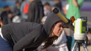 Una niña observa el eclipse con un telescopio