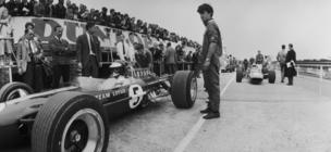 Jim Clark (pictured left in his Lotus car) , his fifth British Grand Prix win and his last. Lotus boss Colin Chapman looks on with arms folded (left)