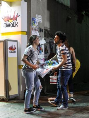 Volunteers stick posters on Beirut walls