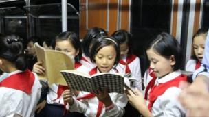 प्योंगयांग मेट्रोतून घरी जाताना शाळेतील मुलं.
