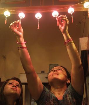 ઘરનાં દ્વારે એલઇડી લાઇટનું તોરણ લગાવતી મહિલા