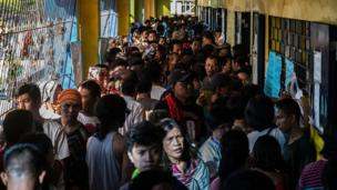 Dozens of people in a queue to vote at a polling station in Manila