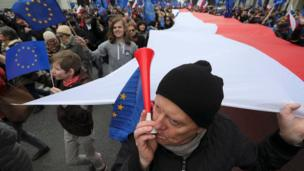 """A man blows a horn during a march called """"I love Europe"""" to celebrate the 60th anniversary of the Treaty of Rome in Warsaw, Poland March 25, 2017"""