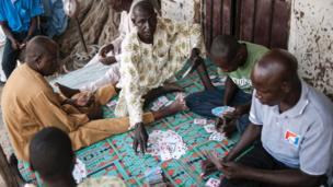 Men play a game of cards in Mbalala, Borno State northeast Nigeria on March 25, 2016. On April 14, 2014, Boko Haram militants kidnapped 276 schoolgirls from their dormitories at the Government Girls Secondary School Chibok, drawing global attention to the Islamist insurgency in northeast Nigeria.