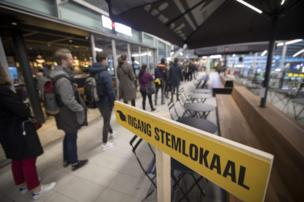 Commuters line up at a voting booth to vote in the Dutch general election at Central Station in Utrecht, 15 March