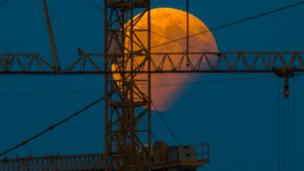 The moon standing in a partial lunar eclipse can be seen behind a constructin crane on August 7, 2017 in Gilching, southern Germany.