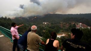 Несколько человек с моста наблюдают за зоной пожара