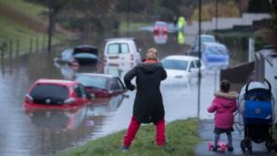 People stop to take a look at cars that have been submerged under nearly a metre of flood water in Bristol. Storm Angus brought hurricane force winds, flooding and power cuts to thousands of homes.