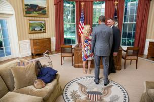 A young boy face-planting himself onto the sofa in the Oval Office