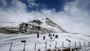 Children sledge in a field near the A93 in Scotland as the snow gates on the A93 at Spittal of Glenshee are closed due to snow