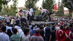 People gather on top of a Turkish military tank in Ankara