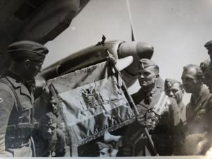 The flag of the Condor Legion - with similarities to the flag of Franco's Spain - is held by troops at an airfield