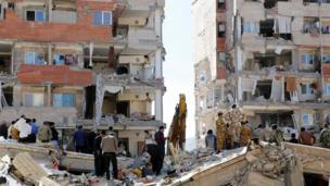 Iran people and soldiers stand around buildings wey don damage