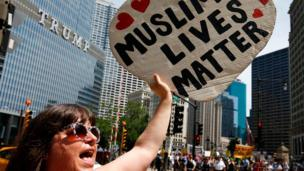 """A woman waves a """"Muslim lives matter"""" placard outside the Trump building in Chicago"""