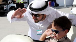 Crown Prince of Dubai, Sheikh Hamdan bin Mohammed bin Rashid al-Maktoum, poses for a picture with a child during the Dubai Airshow on November 14, 2017, in the United Arab Emirates