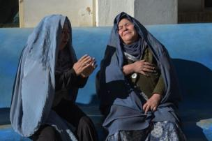 Two Afghan women weep for their relatives at a hospital following explosions at a cultural centre in Kabul in 2017
