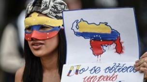 """متظاهرة تحمل لافتة كُتب عليها: """"لا يمكننا الحصول على وطن آخر"""""""