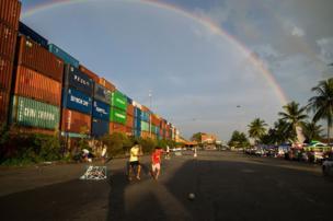 Boys play football underneath a rainbow