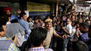 दिल्ली में एक बैंक के बाहर कतार तोड़ने वाले लोगों को डांटता पुलिसमैन