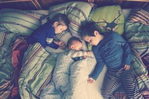 Three boys in their parents bed