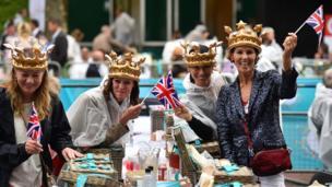 Women don royal crowns while waving British flags at their picnic