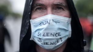 "A man with a ""Don't Silence Science"" mask"