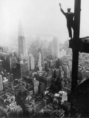 Un obrero saluda desde la estructura de acero del Empire State. Se observa Nueva York al fondo.