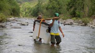 Two Filipino villagers carry a box containing an electronic voting machine, across a river, on Sunday, in the far flung community of North Upi, Maguindanao Province