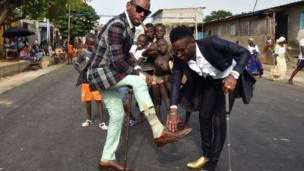 """Les """"sapeurs"""" à Abidjan au Femua, rendent hommage à Papa Wemba, musicien qui était connu pour son élégance."""