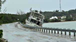 A boat sits washed up along the shore after breaking free of its mooring in the aftermath of Hurricane Matthew on the island of Exuma