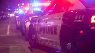 Row of police cars with lights on in Dallas, Texas - July 2016