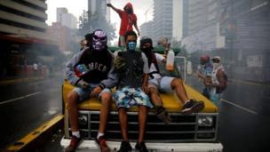 متظاهرون ملثمون يجلسون فوق سيارة