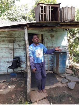 Un hombre frente a una casa miseria