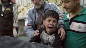 A Syrian boy is comforted as he cries next to the body of a relative who died in a reported air strike on 27 April, 2016 in the rebel-held neighbourhood of al-Soukour in the northern city of Aleppo.