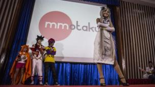 A woman in a cosplay dress stands on stage, in front of three other waiting participants, during the event